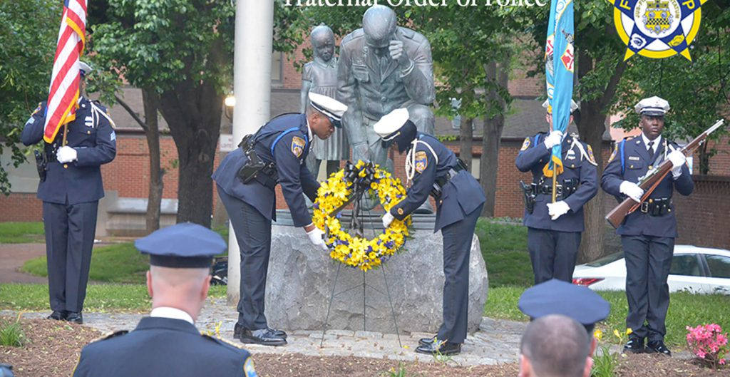 two police officers putting wreath on statue