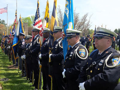 line of police officers stand with flags